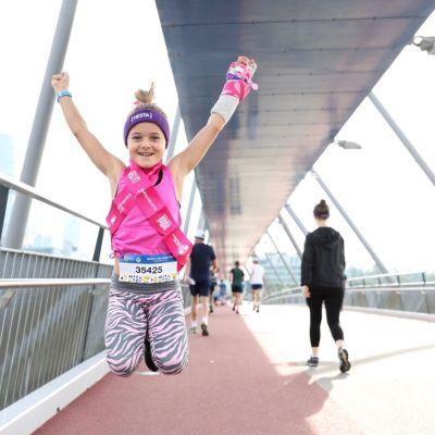 girl jumping in celebration at fun run in QLD