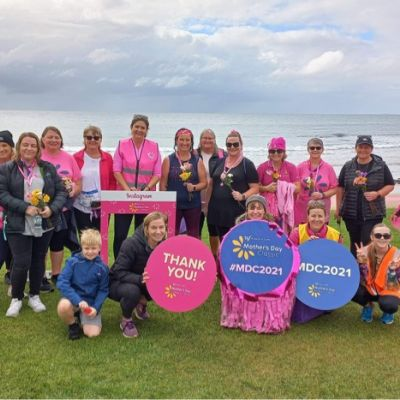 Women gathering outdoors at charity event for breast cancer research