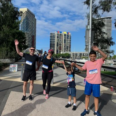 Family with arms in air during charity walk in Melbourne